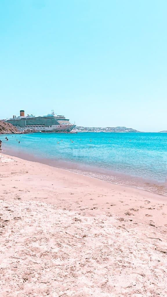 Agios Stefanos Beach Kreuzfahrtschiff im Hintergrund